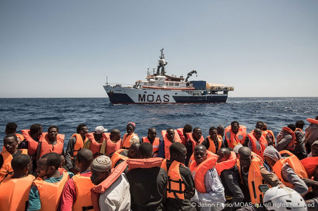 migrants-in-unstable-boat-in-Central-Mediterranean-waiting-to-be-rescued-my-phoenix-in-the-background-copyright-Jason-Florio_MOAS-2016-6585