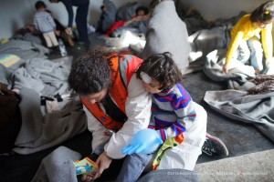 CISOM volunteer Dr Giada helps a wet and cold Syrian child put on dry socks in a refugee center in Agathonisi