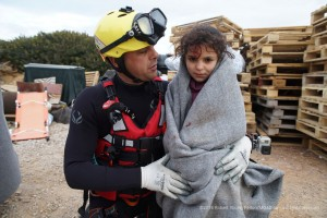 MOAS rescue swimmer Ripley Davenport carries a young Syrian refugee from a fisherman's shack on the remote eastern edge of Agathonisi where her family had sought refuge in the freezing cold after a dawn shipwreck.