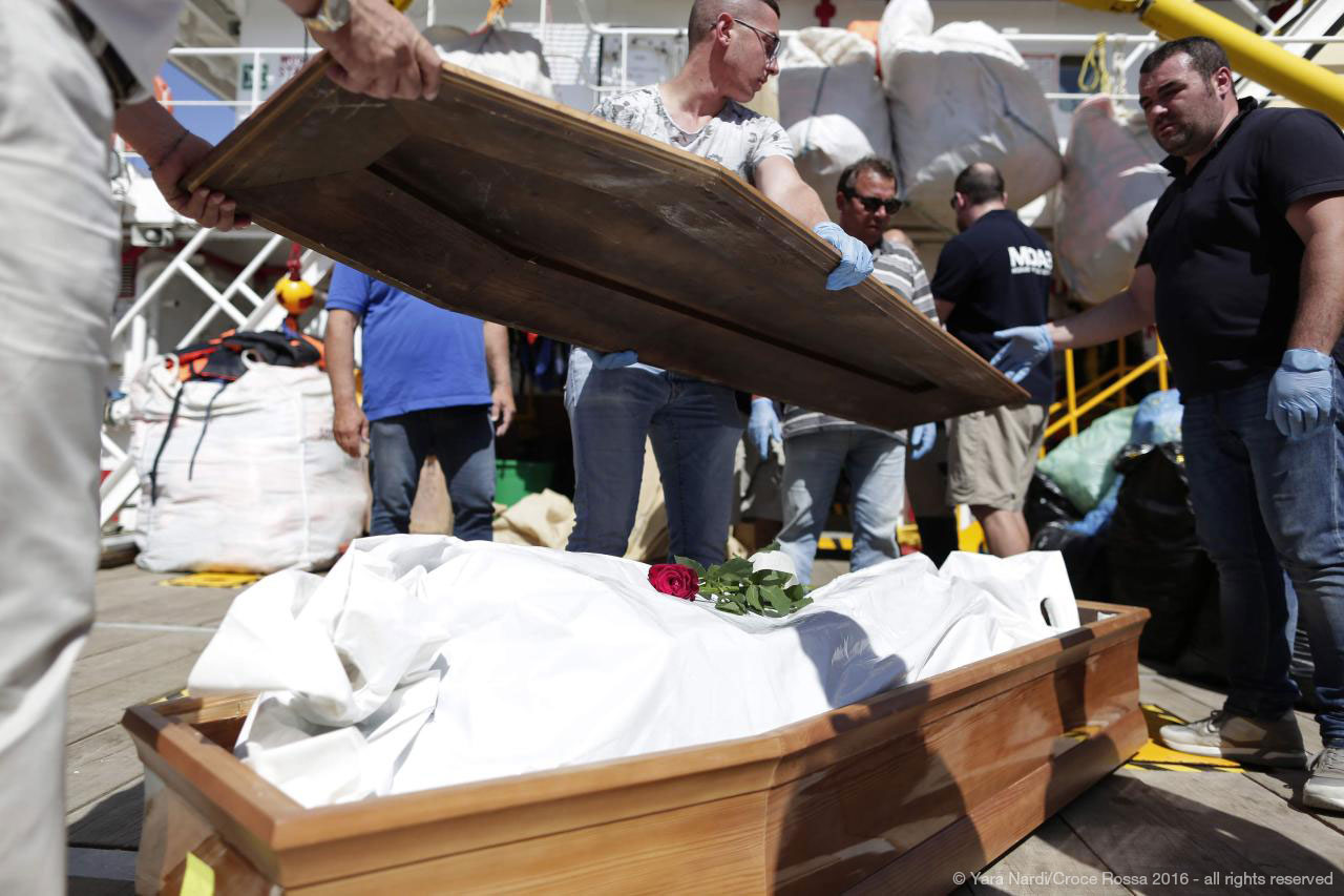 Roses were laid on the bodies of the victims before being transported off the MOAS search-and-rescue vessel, Responder, in Trapani, Sicily.