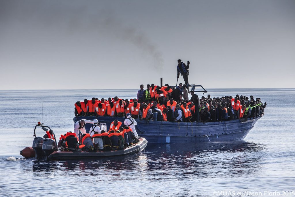 As some are taken to safety, other refugees and migrants on board a heavily overcrowded wooden boat eagerly wait for their chance to reach the safety of the Phoenix.