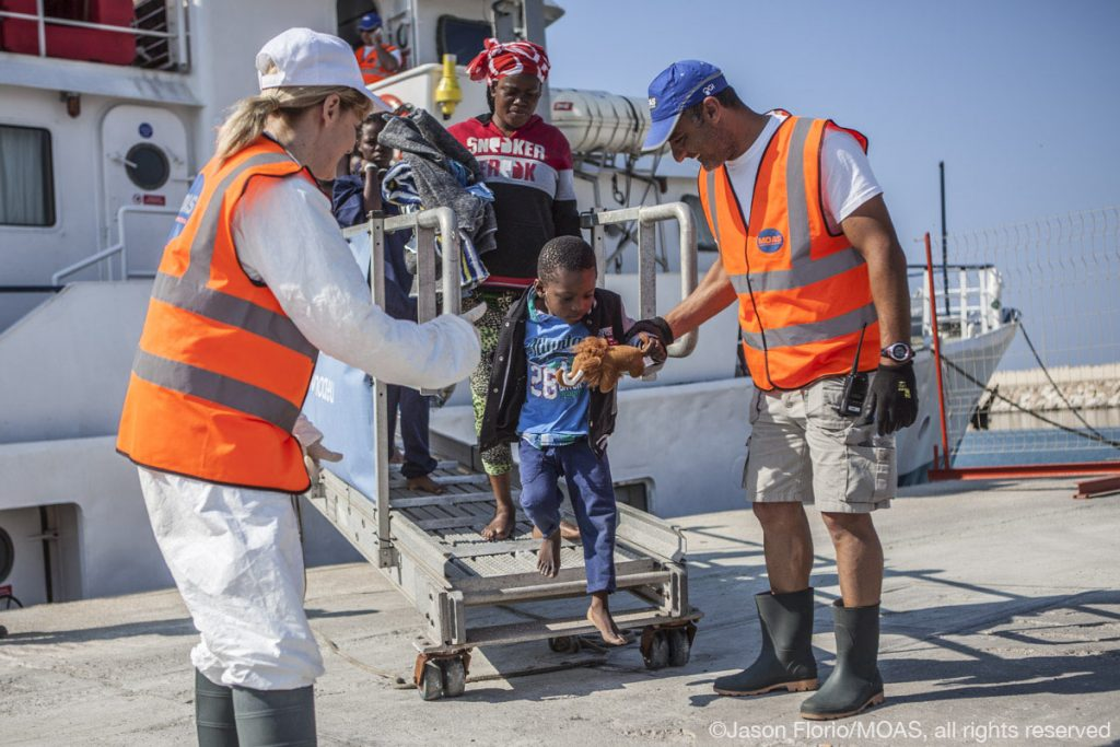Crew member Mimmo, and MOAS co-founder and Director Regina Catrambone help a young boy and his mother off of the Phoenix as they disembark in Sicily.