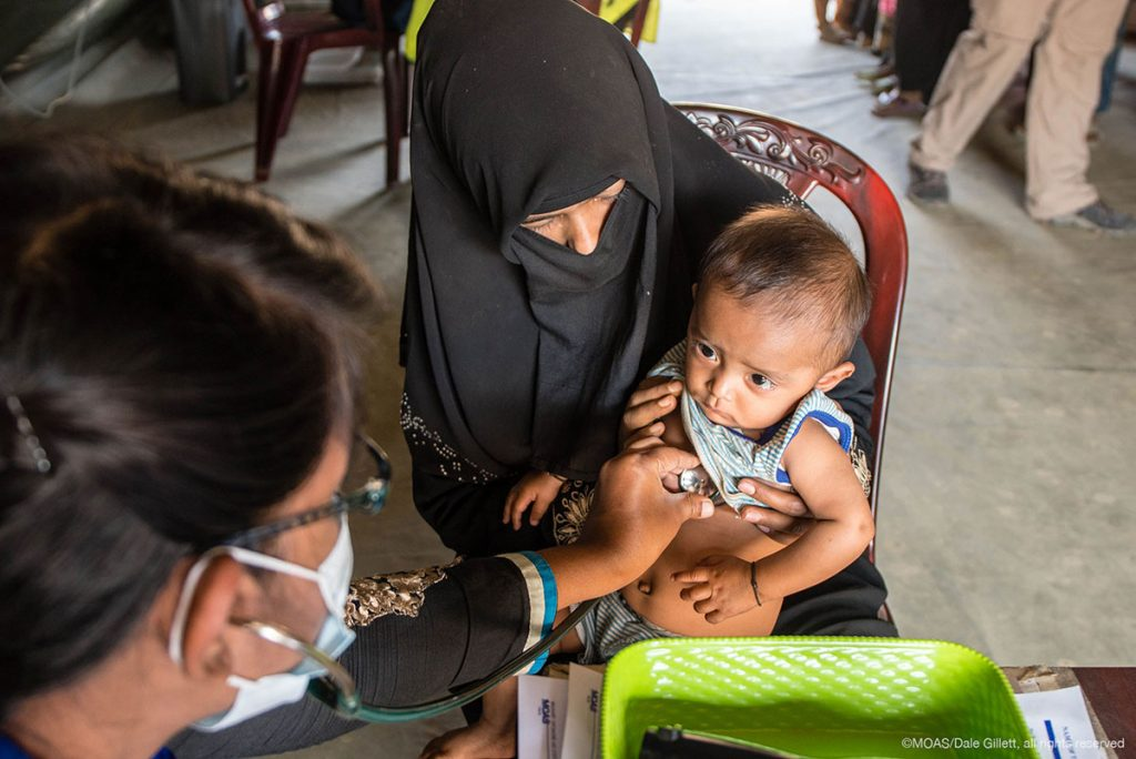A MOAS doctor checks over a young rohingya child who had been brought into the MOAS Aid Station by his worried mother.