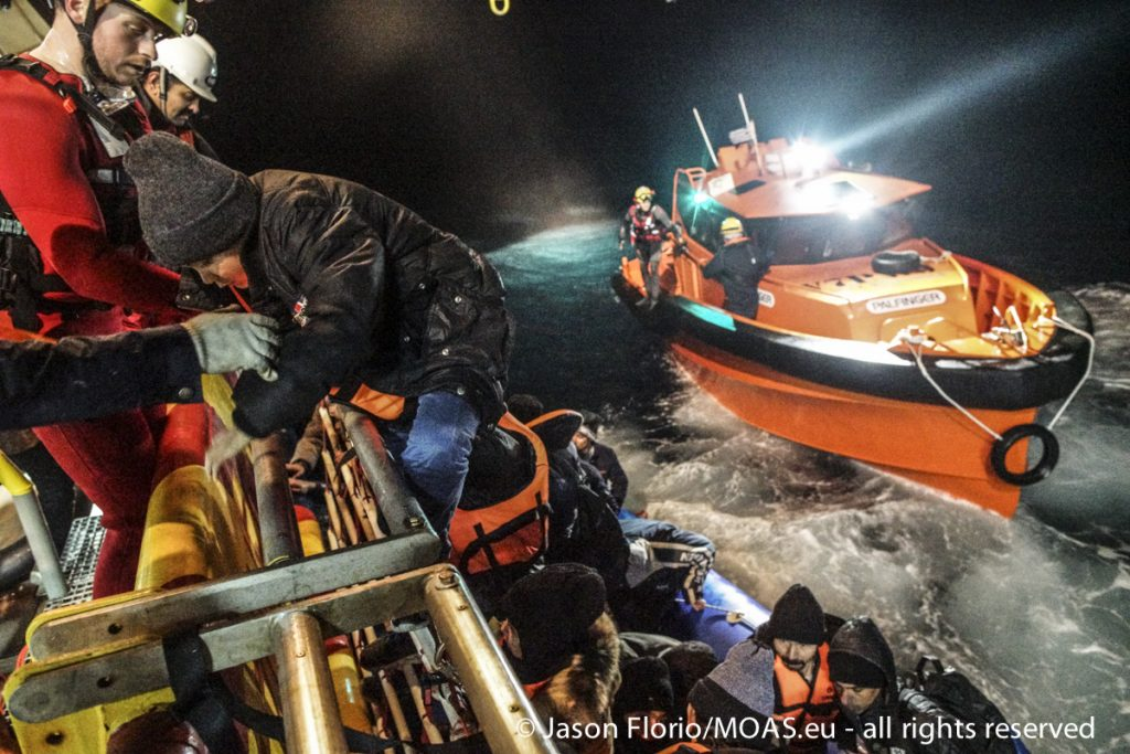Helped by MOAS crew, a child climbs onto the Responder from a rubber boat in the Aegean Sea.
