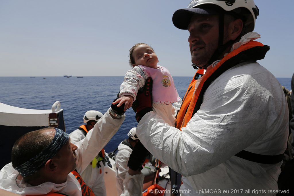 An infant is brought on board the MOAS rescue ship Phoenix, after being rescued along with her mother and father and numerous other refugees and migrants.