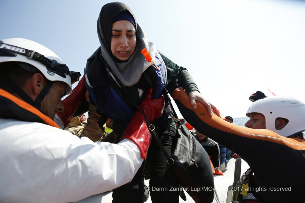 Scared and afraid, a young woman is helped onto the rescue RHIB by MOAS crew after spending hours at sea in a rubber boat with hundreds of people on board.