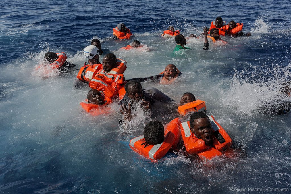 A MOAS rescue swimmer attempts to help several people who had fallen overboard from a rubber boat in the Central Mediterranean.