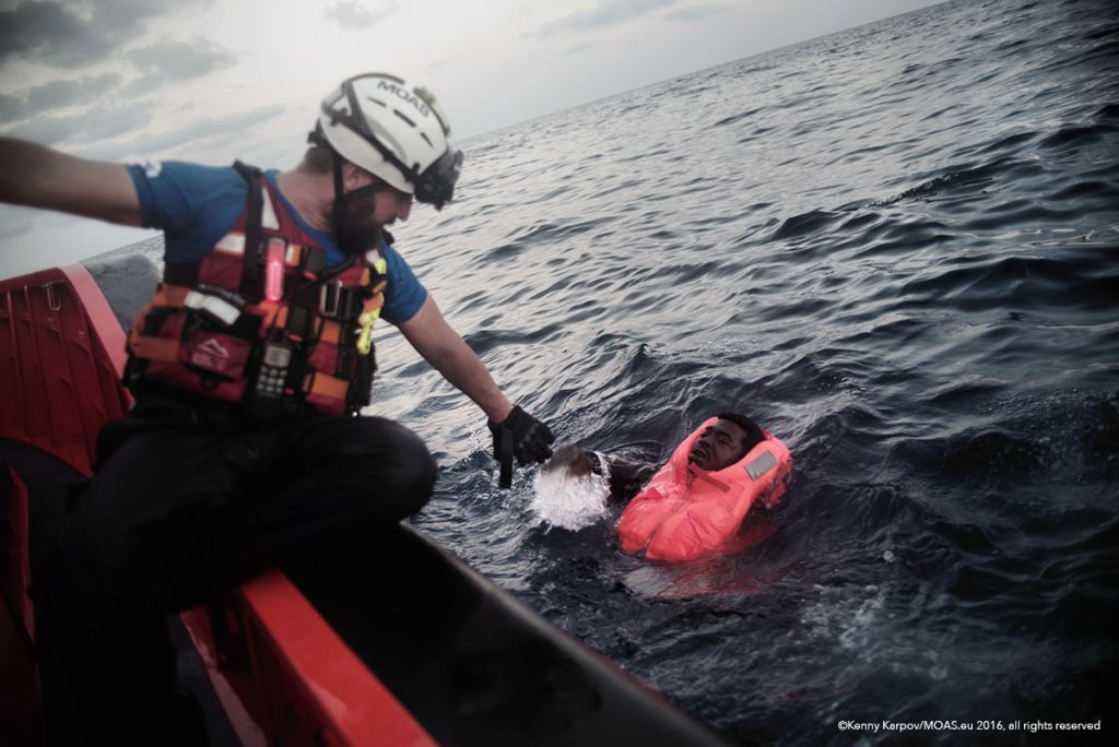 Just in time, a MOAS rescuer reaches a man who had fallen into the sea after falling from a packed boat.
