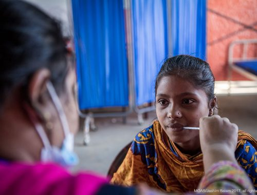 A young girl has her temperature taken by a MOAS nurse in Shamlapur Aid Station.