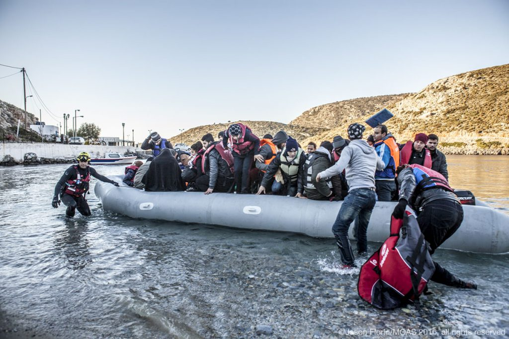 After reaching the Greek island of Agathonisi, migrants and refugees are helped onto the island.