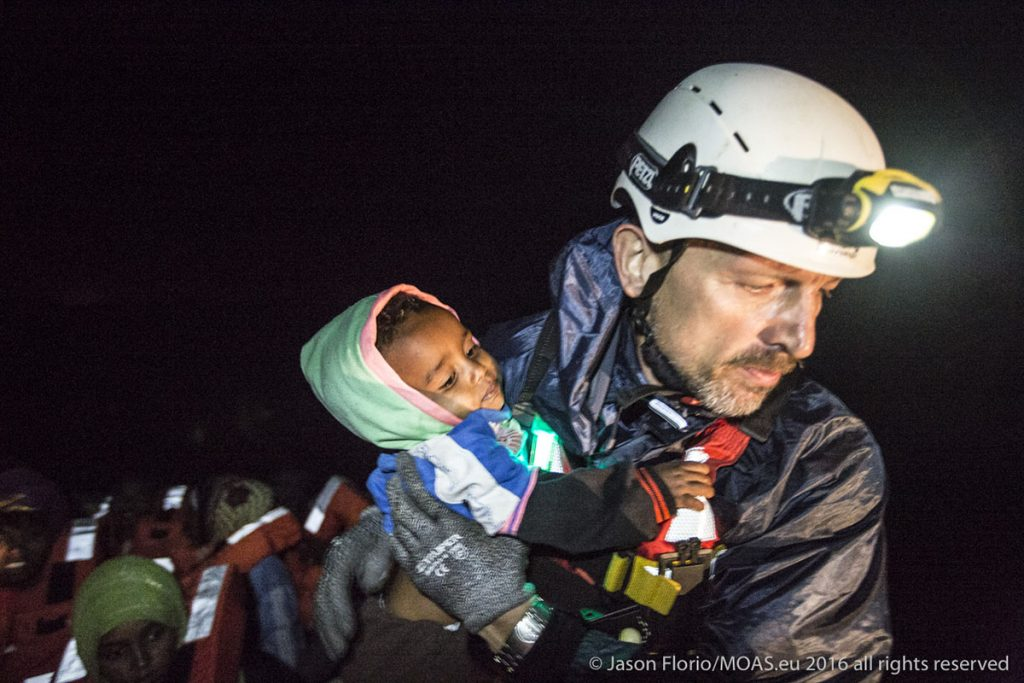 Igor, a MOAS crew member, carefully helps a young child off of a rickety boat and onto the safety of the Phoenix.